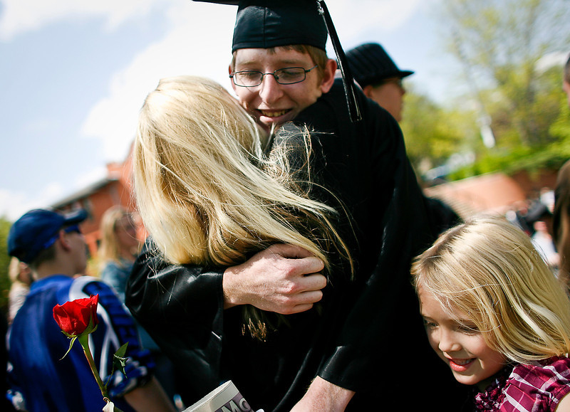 Ferguson High School graduate Max Gates hugs his sister, Noel McNally, left, and niece Kaya McNally, 7, following the graduation ceremony at Foote Lagoon, on 3rd Street and Washington Avenue Thursday afternoon.