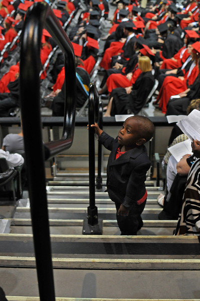 GC Onuoha, 20 months, preoccupies himself with the crowd, Sunday, during Loveland High School's graduation ceremony at the Budweiser Event Center.  His graduating sister, Ezinne Onuoha, recently placed 8th in the 100m dash at the state track competition.