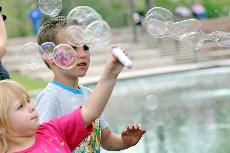 Fort Collins resident Lilliena Parry, 2, left, and Samuel Woodward, 5, of Loveland play with bubbles coming out of a bubble machine Saturday at Foote Lagoon during the Cinco de Mayo Celebration.