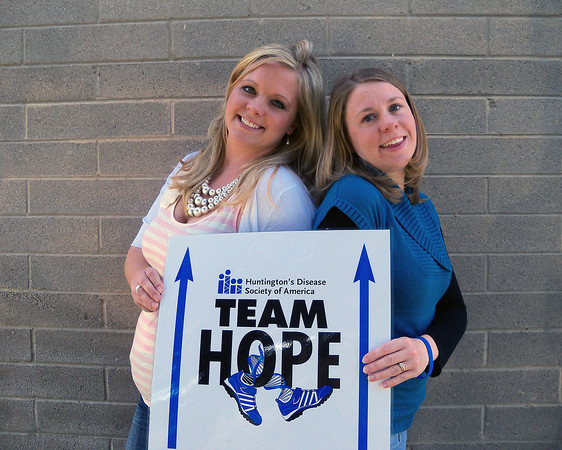 Jenna Schaefer and Desiree Luca,  event co-chairs for A Walk in the  Park, hold up a sign for the 1.3- mile fundraising walk Saturday to  help support the Huntington's  Disease Society of America.