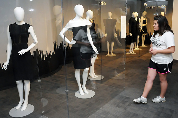 Colorado State University freshman Grace Padilla looks at dresses Friday on display at the Avenir Museum of Design and Merchandising, 1400 Remington Ave. in Fort Collins as part of an exhibit called The Little Black Dress: 85 Years of Effortless Style and Elegant Mystery.