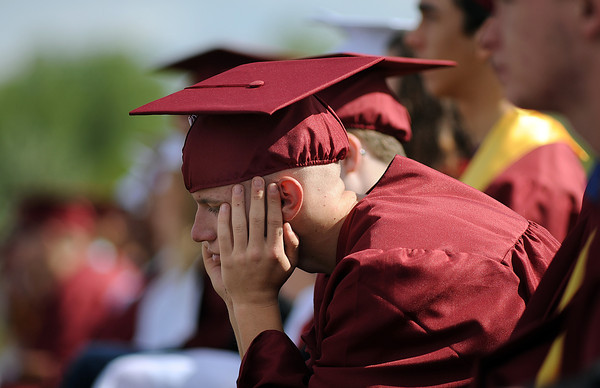 Jamith McClure, 18, listens to speeches as he waits to get his diploma during the Berthoud High School graduation at Max Marr Field on Saturday, May 21.