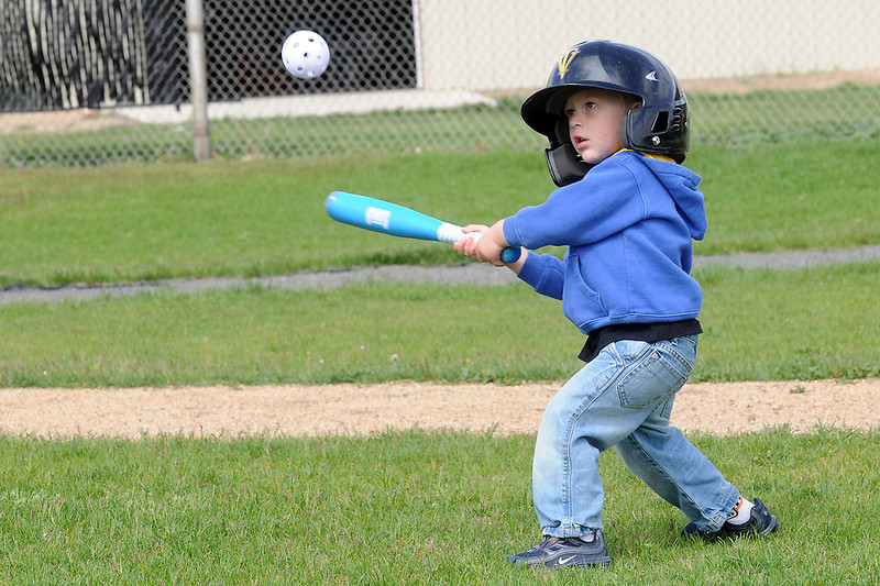 Two-year-old Cameron Denning eyes the ball as he prepares to swing at a pitch thrown by his dad, Jay, while they play together Saturday morning near Thompson Valley High School.