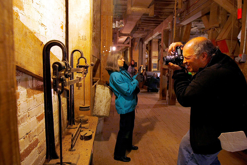 Bob Campagna and Ruth Soller take photos inside of the Loveland Feed and Grain building in Loveland.  Campagna, president of Novo Restoration,  organized the tour for photographers to tour and photograph the inside and outside of the historic landmark. (Photo by Gabriel Christus)