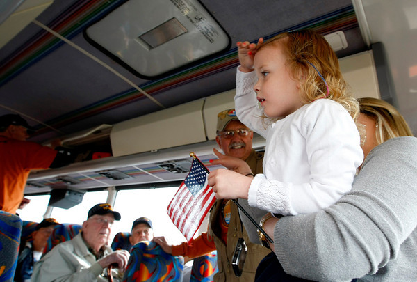 Rosalie Thim takes Averie Parish, 3, on one of the busses to salute the Vets before their departure on Sunday at the Embassy Suites in Loveland. (Photo by Gabriel Christus)