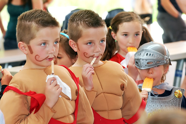 Eight-year-old Aaron Burdick, left, and his twin brother, Greg, are dressed as muscle men as they finish up their ice cream after participating with other children in the Pet and Doll Parade on Friday at Fairgrounds Park.