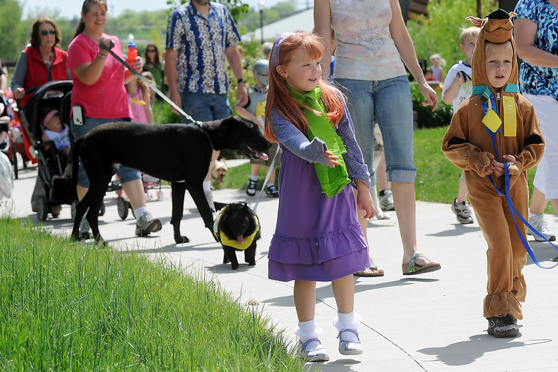 Jayden Bruce, 5, right, wears a Scooby Doo costume as he walks along the parade route with Audrey Jones who's dressed as the character Daphne from the cartoon during the Pet and Doll parade Friday afternoon a Fairgrounds Park.