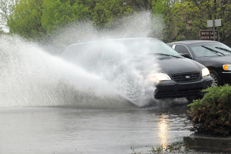A vehicle splashes water in the air after hitting a puddle while driving west near the Enterprise Rent-A-Car located at 1117 E. Eisenhower Blvd. in Loveland.
