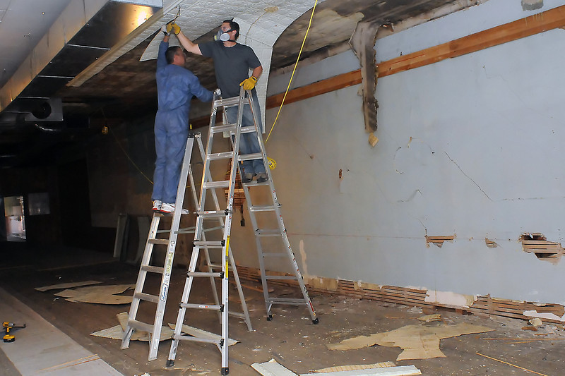 Matt Kaufman, left, and Pat Coen remove tin ceiling tiles Friday inside the Quality Shoe building in the 200-block of East Fourth Street in downtown Loveland. The building will be demolished to make way for the Rialto Bridge project and some of the material inside is being recycled and reused.