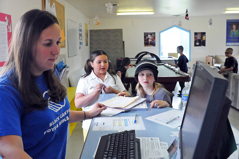 Christy Doyon, left, assists Cora Cienfuegos-Baca, 10, and Larissa Otenberger, 10, as they check in  at the Boys and Girls Club of Larimer County, Wellington Unit on Friday afternoon.
