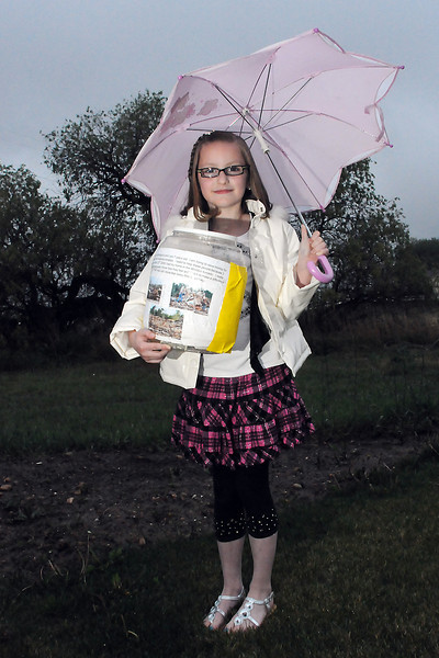Seven-year-old Aria Billingsley poses outside her Loveland home while holding the large jar she used to collect money to donate to the American Red Cross. Aria raised $601.00 which will be earmarked for victims of the recent tornado in Tuscaloosa, Alabama.