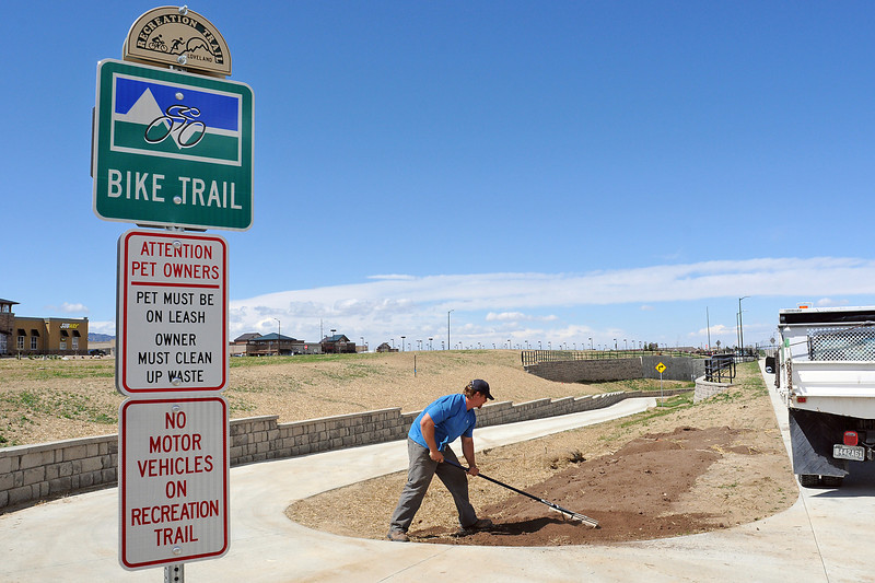 City of Loveland parks worker Paul Foreman spreads dirt along the bike trail before seeding the area Wednesday in north Loveland near the new underpass at U.S. 287 and 57th Street.