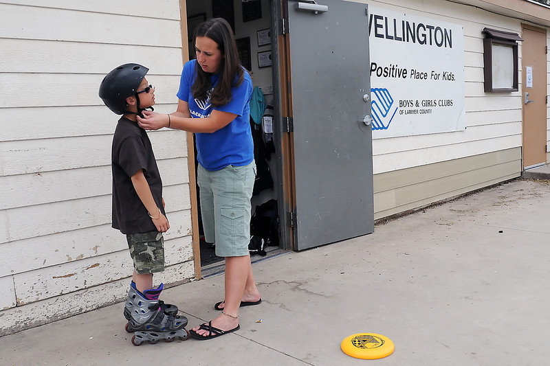 Seven-year-old Garrett Dulany gets some help with his helmet from Christy Doyon before he went skating Friday at the Boys and Girls Club of Larimer County, Wellington Unit.