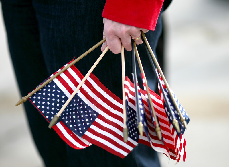 Pam Allen holds a handfull of American Flags after waving goodbye to the Vets on their way to Washington DC on Sunday at the Embassy Suites in Loveland. (Photo by Gabriel Christus)