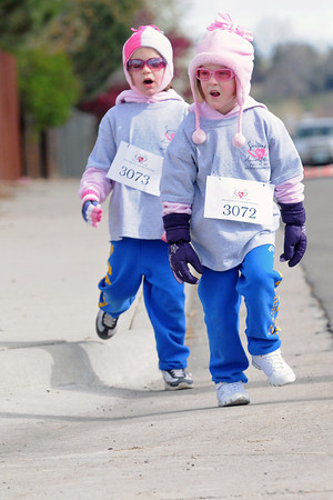 Ellie Peters, 4, front, and her sister, Nicole Peters, 6, are bundled up against the morning chill on Saturday as they walk together during the Sierras Race for the Cure 5K Run/Walk in Loveland.