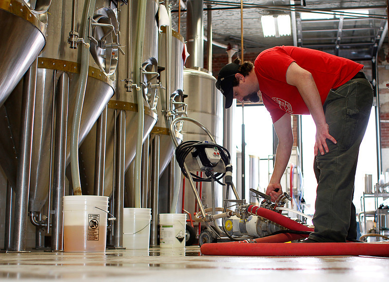 "Loveland Aleworks head brewer Nick Callaway adjusts their ""clean in place"" pump Monday while pumping a sanitizing solution through a vacant fermenting tank at Loveland Aleworks in downtown Loveland."