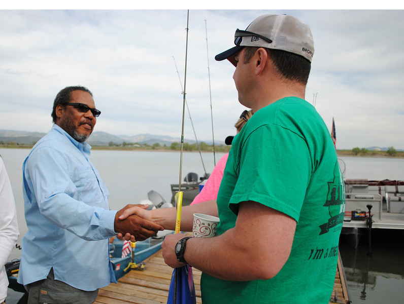Vietnam veteran, Valentine Roberts (left) and David Sears (right) introduce themselves before heading out in the boats for a day of fishing, at Loveland lake, during the Warriors on the Lake event on Saturday May 18, 2013. (photo by Lilia Munoz)