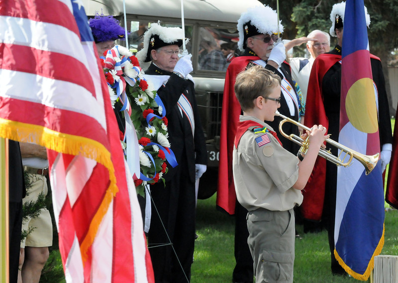 Members of the Knights of Columbus salute as a Boy Scout plays taps at the end of a Memorial Day service at the Vietnam Veterans Shrine outside St. John the Evangelist Catholic Church in Loveland on Monday, May 27, 2013. (Photo by Craig Young)