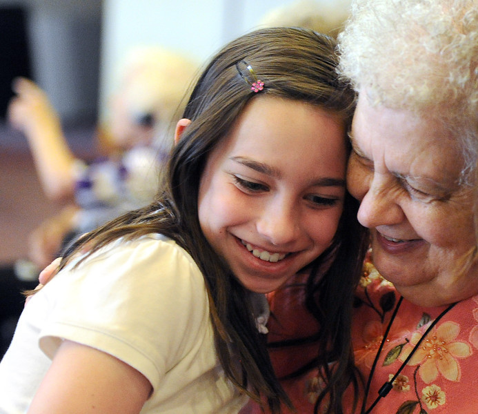 Colette Williams, 10, a fourth-grader at  HMS Richards Adventist School on the Campion Academy campus in Camion, gets a hug from resident Sharon Bucklen at the Good Samaritan Village in Loveland on Wednesday, May 15, 2013. Students from the school had their last visit for this school year with their adopted grandparents at Good Samaritan Village.