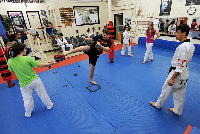 Olympic athlete Farkhod Negamatov from Tajikistan, right, looks on while teaching taekwondo students, front from left to right, Natalie Gendill, Tristan Feilinger, Nina Kentwortz and Tristin Campbell a kicking technique during an event featuring national team athletes from Iraq and Tajikistan on Tuesday, May 14, 2013 at Koran Academy of Taekwondo in downtown Loveland.