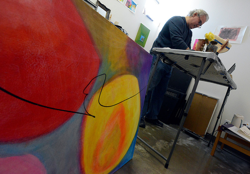 With one of his mixed-media pieces in the foreground, Andrew Svedlow uses oil pastels in his studio at Artworks Loveland on Friday, May 3, 2013 in downtown Loveland. Artworks Loveland is a non-profit where artists rent studio space and work in a community type environment.