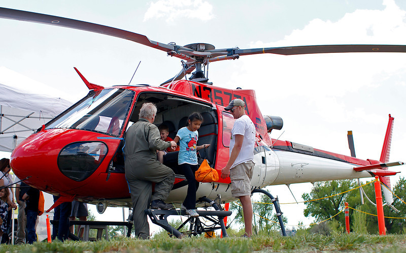 Maria Chino (8) is helped out of a helicopter by Loveland Airport line-service technician David Kaminky, right, and Chief Pilot Jim Hennessy, Tuesday morning at Loveland's 10th Annual Public Works Day at Fairgrounds Park.