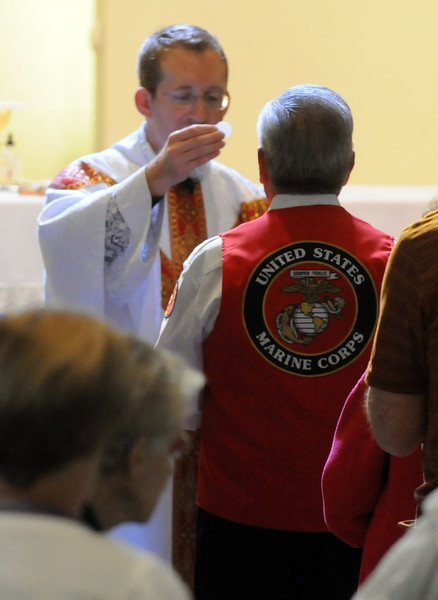 A man wearing a U.S. Marine Corps vest receives Communion from the Rev. Sam Morehead during a Memorial Day Mass at St. John the Evangelist Catholic Church in Loveland on Monday, May 27, 2013. (Photo by Craig Young)