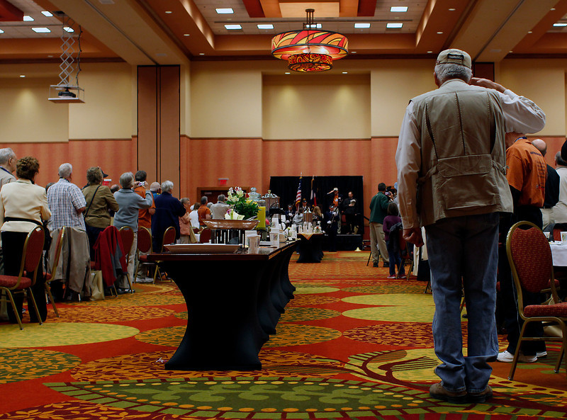 """A veteran salutes the colors during the National Anthem at the Embassy Suites Loveland Sunday morning. This ceremony took place as part of """"Honor Flight Northern Colorado"""" where U.S. veterans are bussed to Denver International Airport, from where they will fly to Washington, D.C., to visit war monuments."""