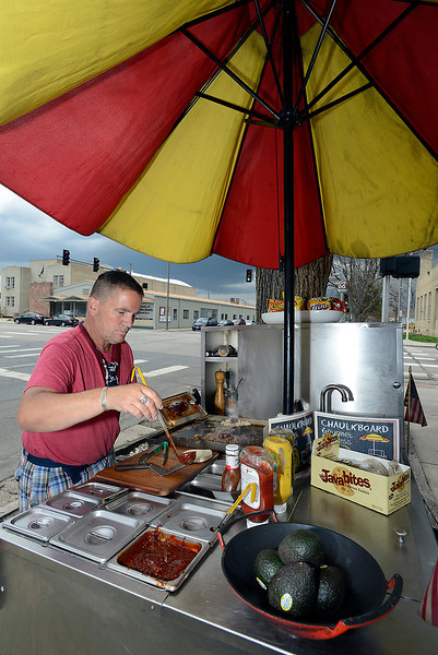 Billy Daniels, owner of Chaulkboard Gourmet Express food cart, adds some of his home-made red chili to tacos for a customer on Sixth Street and Cleveland Avenue in downtown Loveland on Thursday, May 9, 2013. Daniels, a gourmet chef who spent 20 years in corporate food service, pulls his food cart behind a bright yellow Mini Cooper to breweries and businesses in the area.