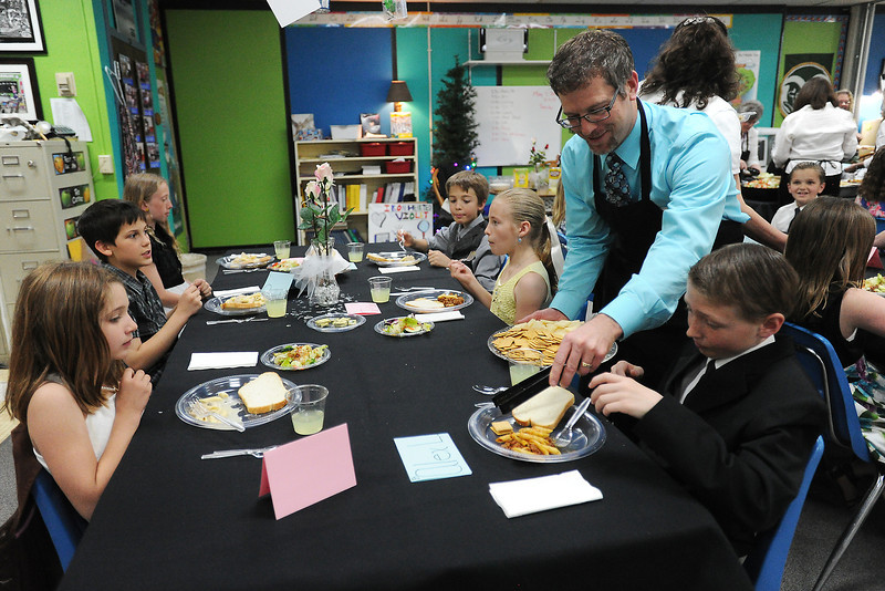 Carrie Martin Elementary School fourth-grader Alex Lawrence, 10, right, is served some crackers and cheese by parent volunteer Greg Dewey while he dines with classmates, clockwise from front left, Claire Harkenrider, 9, Quade McLeran, 10, Summer McGuire, 10, Jonah Gustafson, 10, and Taylor Adamson, 10, during an etiquette luncheon Wednesday at the school.