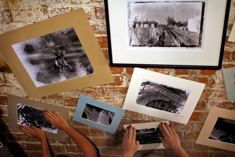 Megan Hurr, left, and Greta Stellrecht press black and white photographs onto the walls of the Loveland Feed & Grain building Tuesday afternoon in Loveland, Colo.
