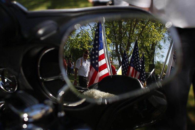 Retired veteran and Honor Guard Monty Long, center, visits with other veterans near his motorcycle, laden in patriotic gear, Monday morning after a Memorial Day ceremony honoring U.S. armed forces at Loveland Burial Park. (Photo by Timothy Hurst)