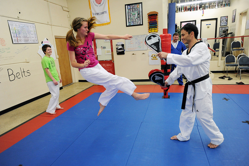 Tristin Campbell, left, spars with Khusrav Giyosov during an event Tuesday, May 14, 2013 at Korean Academy of Taekwondo, 106 W. Fourth St. in downtown Loveland.
