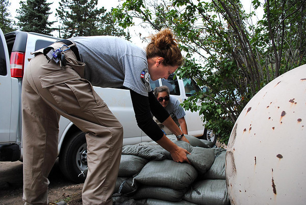 Americorps volunteers, Amy Tyilliann, front, and Ashley Sandmann, back, place sandbags around a home in Poudre Park to help protect it from flooding on Monday May 20, 2013.