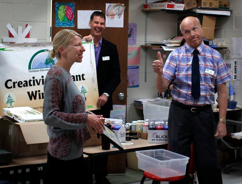 "Thompson Education Foundation former president Stu Boyd, right, gives his approval to the awarding of the foundation's ""Creativity Grant"" to art teacher Megan Henderson, left, while board director Gordan McQueen looks on Tuesaday morning during Henderson's first class at Ivy Stockwell Elementary School in Berthoud, Colo."
