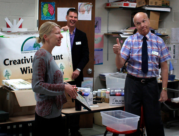 """Thompson Education Foundation former president Stu Boyd, right, gives his approval to the awarding of the foundation's """"Creativity Grant"""" to art teacher Megan Henderson, left, while board director Gordan McQueen looks on Tuesaday morning during Henderson's first class at Ivy Stockwell Elementary School in Berthoud, Colo."""