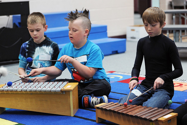 Mary Blair Elementary School fourth-graders Ethan Lenz, 10, left, and Dylan Gibson, 10, play a metallophone while Garrett Kash, 10, plays on a xylophone in the music room on Thursday, May 2, 2013. The Thompson School District received a donation to repair instruments all through the district and these instruments are some could be fixed up.