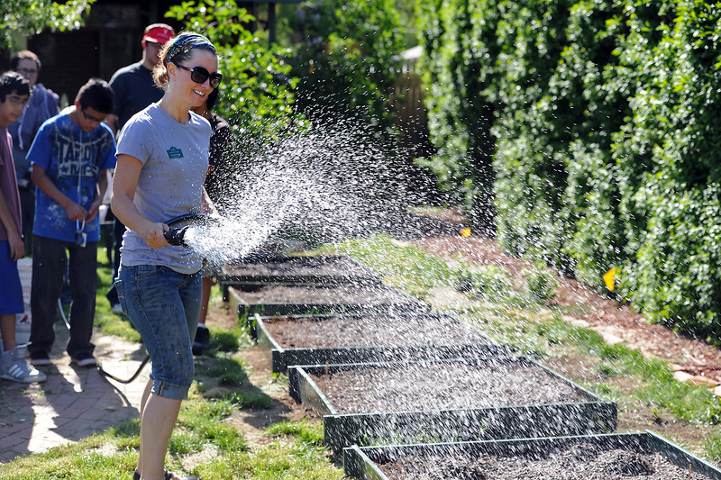 Alyssa McConkey, program director for the Loveland Youth Gardeners, left, sprays garden beds with a hose after a she and a group of Youth Gardeners prepped and planted vegetables in a resident's yard in Loveland for the Plant a Row program on Wednesday, May 22, 2013.
