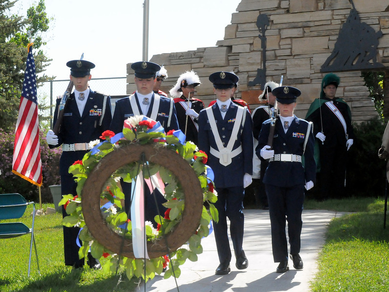 Members of a Civil Air Patrol color guard march back to their positions after posting the colors during a Memorial Day ceremony at the Vietnam Veterans Shrine outside St. John the Evangelist Catholic Church in Loveland. From left they are Cadet Capt. Walter Bordewyk, 17, Msgt. Derek Lantis, 16, Chief Msgt. Noah Bordewyk, 13, and color guard commander Sydney Dunnahoo. (Photo by Craig Young)