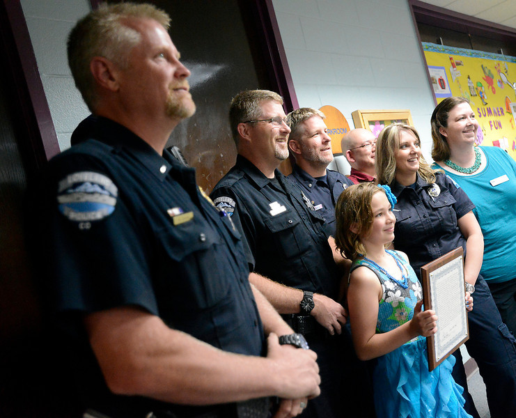 "Third-grader Tara Homola, 9, center, is surrounded by Loveland Police officers, Thompson Valley EMS EMT's and her parents after receiving an award Wednesday, May 29, 2013 from the Loveland Police Department at her school, Mary Blair Elementary, for saving her mom's life. On Tara's birthday, March 14, 2013, her mom, Bridget Homola, had a medical emergency due to low blood sugar. Tara called 911 and told dispatchers about her mom's condition, kept her little brother calm, waited for emergency personnel and much more. Her mom Bridget Homola said ""She saved my life! I wouldn't be here today if she  didn't know what to do. I'm so proud of her!"" From left are Loveland Police Lt. Rick Arnold, Loveland Police officer Gary Patzer, Thompson Valley Emergency Medical Services EMT's Todd Gates and Andrea Emmerling, Tara's dad and mom, Brian and Bridget Homola."