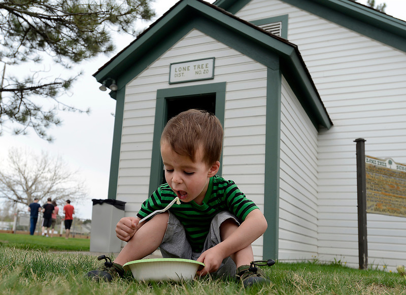 Levi Daly, 2, takes a bite of his ice cream as he sits in front of the Lone Tree School  at North Lake Park during an ice cream social held by the Loveland Museum/Gallery in Loveland on Wednesday, May 15, 2013.