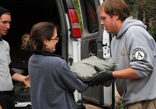 Americorps volunteer Meg Conely, center, shares a laugh with Shawn Decker, right, and Russ Lee as they unload sandbags from a van in Poudre Park on Monday May 20, 2013. They came to help residents in the town secure their homes from flooding in the High Park fire area.