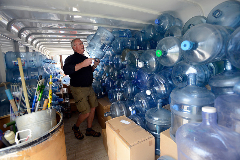 Don Wilson, foundr of H.E.L.P. International, stacks water bottles on top of other supplies in Loveland on Tuesday, May 21, 2013. The trailer, loaded with 150 tents, 500 water bottles, food, toiletries, tools, bedding and more, will be on its way to Oklahoma City to help folks after the tornado.