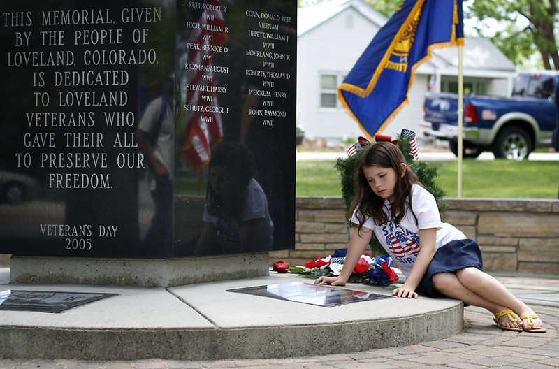 American Legion Auxiliary Unit 2000 member Rebecca Smith (10) reads a plaque on the Loveland Veteran Memorial, Monday morning after a Memorial Day ceremony at Dwayne Webster Veterans Park in Loveland. (Photo by Timothy Hurst)