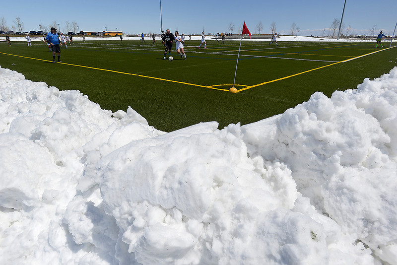 Deep piles of snow surround the turf field at the Loveland Sports Park as the Mountain View High School soccer team plays against Silver Creek High School in Loveland on Thursday, May 2, 2013.