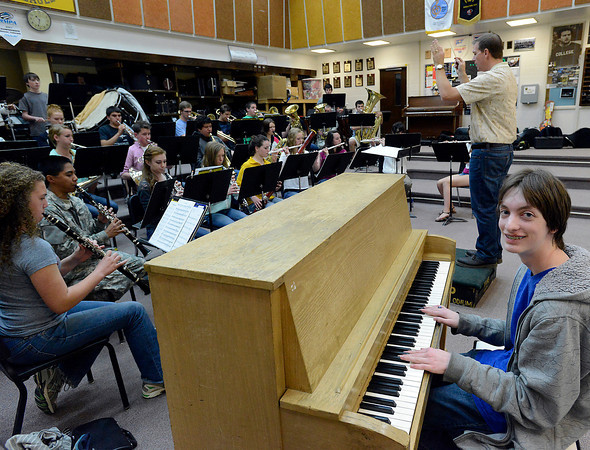 """Thompson Valley High School junior Blake Russell, right, poses for a photo sitting at the piano as band director Robert Pippin leads a class in Loveland on Friday, May 10, 2013. Blake composed a piece, """"Faith: A Dark Storm,"""" which the symphonic band will perform during Pippin's last concert."""