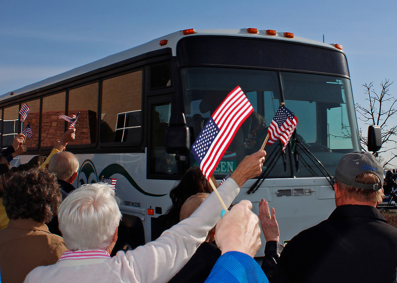 "Supporters wave American flags and cheer as busses carrying 122 veterans pull out of the Embassy Suites Loveland parking lots Sunday morning in Loveland. The veterans, including 25 from Loveland and Berthoud, will be flying to Washington, D.C., to visit war monuments as part of ""Honor Flight Northern Colorado."""