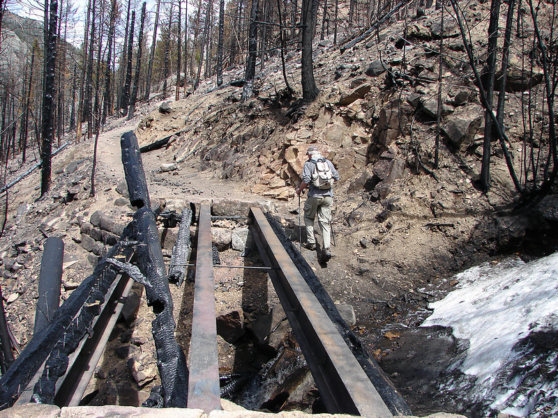A hiker bypasses a burned foot bridge on Fern Lake Trail in Rocky Mounatin National Park on May 13, 2013, on his way eastward to Cub Lake in Rocky Mountain National Park.