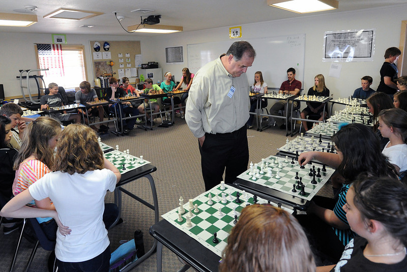 Brad Lundstrom, center, walks around the middle of a circle of desks while playing chess games in an exhibition format against Resurrection Christian School students Thursday, May 16, 2013.