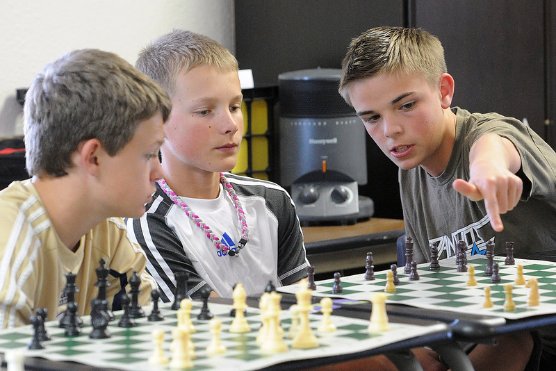 Resurrection Christian School students, from left, R.J. Ells, 13, Trent Beall, 12, and Trenton Brand, 13, discuss chess strategy while their entire classroom plays a game against chess master Brad Lundstrom at the same time on Thursday, May 16, 2013 at the school.
